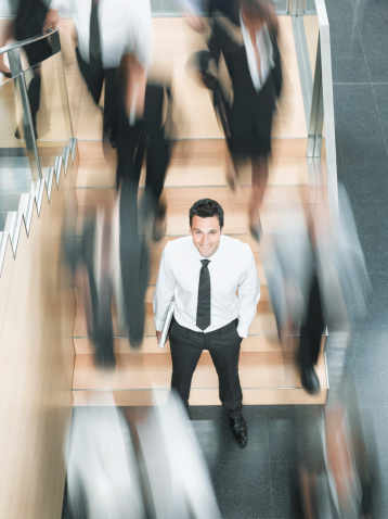 Calm businessman standing in busy office - gettyimageskorea