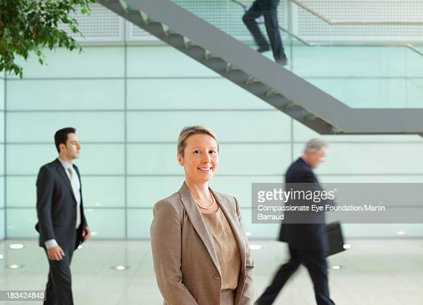 Calm businesswoman standing in busy lobby