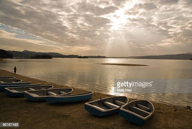 calm cove beach with boats at dusk - ippei naoi stock photos and pictures