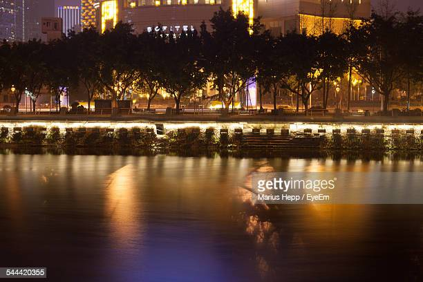 Calm Lake Against Trees And Illuminated Buildings At Night