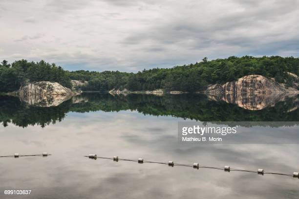 calm lake at dusk with near perfect reflection of the shore in the water - sudbury canada stock photos and pictures