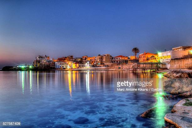 calm lake by residential buildings against clear blue sky at dusk - beirut stock pictures, royalty-free photos & images