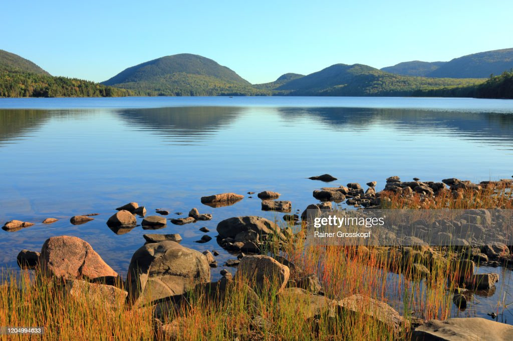 A calm lake on a sunny day with reflections of the surrounding forested hills : Stock-Foto