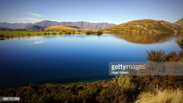 Calm lake with mountains and rural landscape