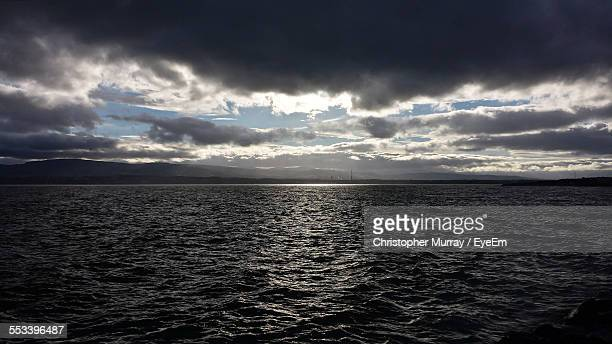 calm sea under dramatic sky - blackrock stock pictures, royalty-free photos & images