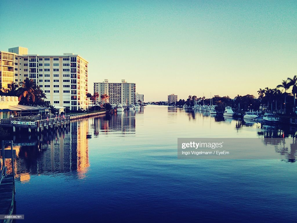 Calm sea with buildings and moored boats in background against clear sky : Stock Photo