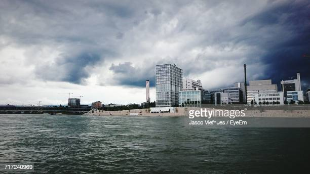 Calm Sea With Buildings In Background Against Cloudy Sky