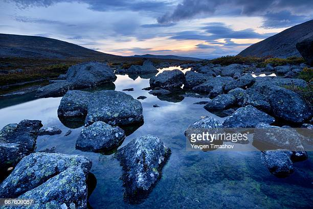 Calm water and boulders at Chasnayok river, Khibiny mountains, Kola Peninsula, Russia