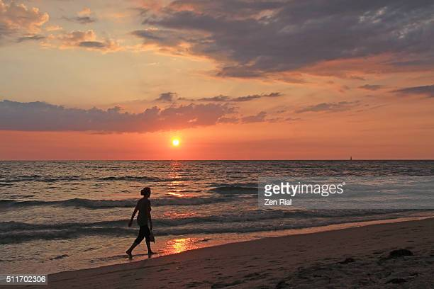 Calming scene of a woman walking on the beach at sunset