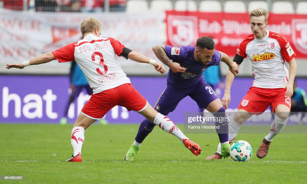 Calogero Rizzuto of Aue is challenged by Alexander Nandzik and Joshua Mees of Regensburg during the Second Bundesliga match between FC Erzgebirge Aue and SSV Jahn Regensburg at Sparkassen-Erzgebirgsstadion on October 22, 2017 in Aue, Germany.