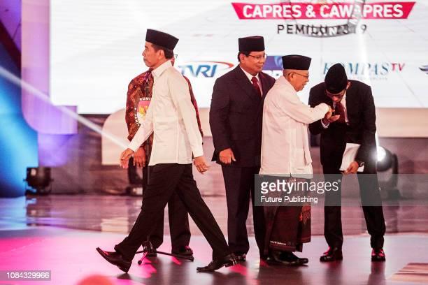 Calon presiden yang berkuasa Presiden Joko Widodo dan pasangannya Maruf Amin berjabat tangan dengan lawan mereka Prabowo Subianto dan pasangannya...