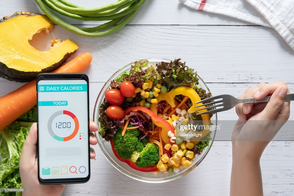 Calories counting , diet , food control and weight loss concept. Calorie counter application on smartphone screen at dining table with salad, fruit juice, bread and fresh vegetable. healthy eating : Stock Photo