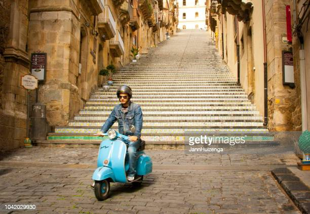 caltagirone, sicily: hip young man on blue vespa scooter - vespa brand name stock pictures, royalty-free photos & images