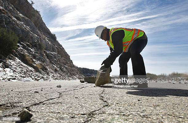 Caltrans spokesman Patrick Chandler removes rocks from a stretch of Highway 39 that has been closed for 30 years. CalTrans plans to legally abandon...