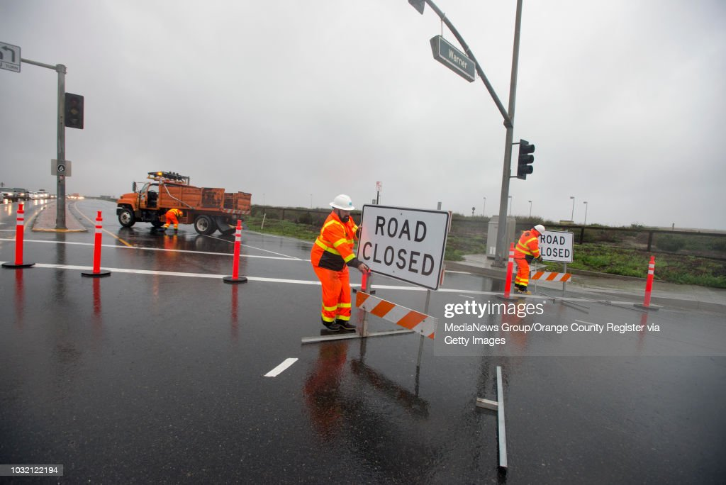A Caltrans worker pulls back a road closed sign after it blew across