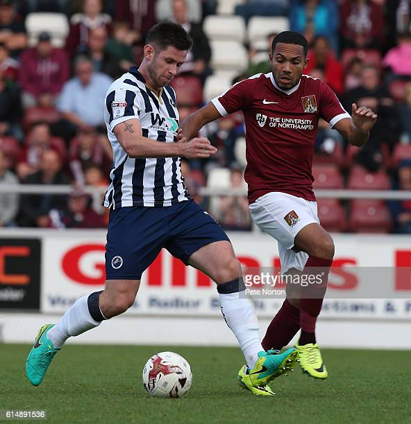 Calum Butcher of Millwall looks to play the ball watched by Kenji Gorre of Northampton Town during the Sky Bet League One match between Northampton...