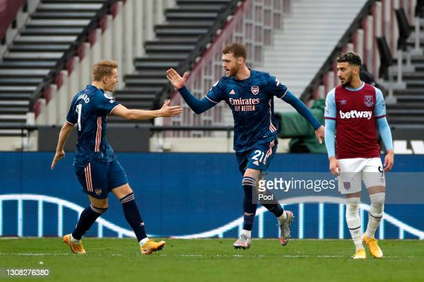 Calum Chambers of Arsenal celebrates his side's second goal with Martin Odegaard during the Premier League match between West Ham United and Arsenal...