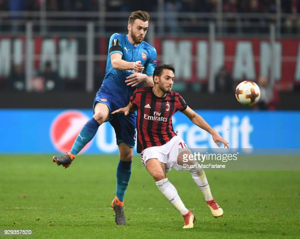 Calum Chambers of Arsenal challenges Haken Calhanoglu of Milan during UEFA Europa League Round of 16 match between AC Milan and Arsenal at the San...