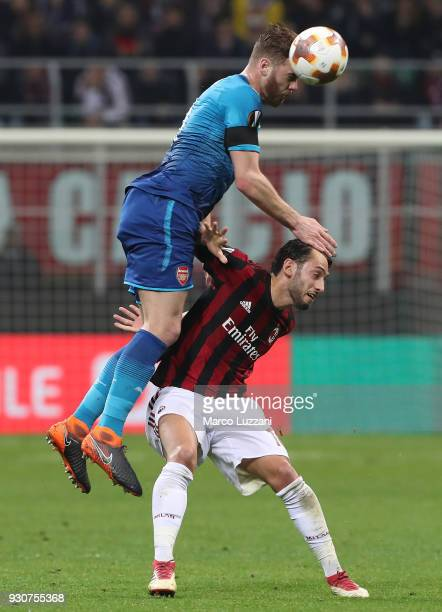 Calum Chambers of Arsenal FC competes for the ball with Hakan Calhanoglu of AC Milan during UEFA Europa League Round of 16 match between AC Milan and...