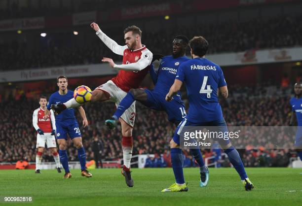 Calum Chambers of Arsenal hooks the ball under pressure from Tiemoue Bakayoko and Cesc Fabregas of Chelsea during the Premier League match between...