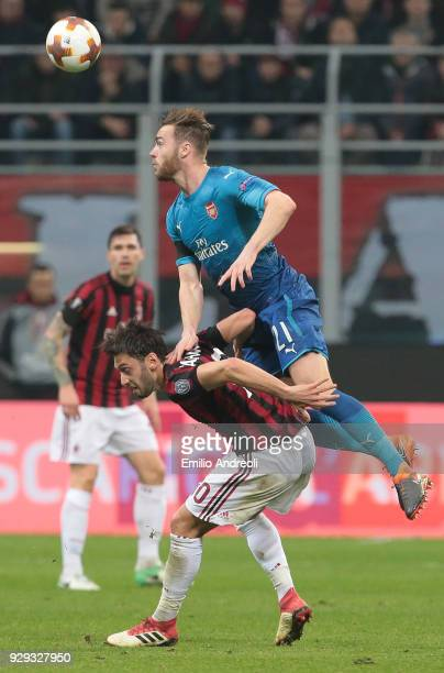 Calum Chambers of Arsenal jumps for the ball against Hakan Calhanoglu of AC Milan during UEFA Europa League Round of 16 match between AC Milan and...