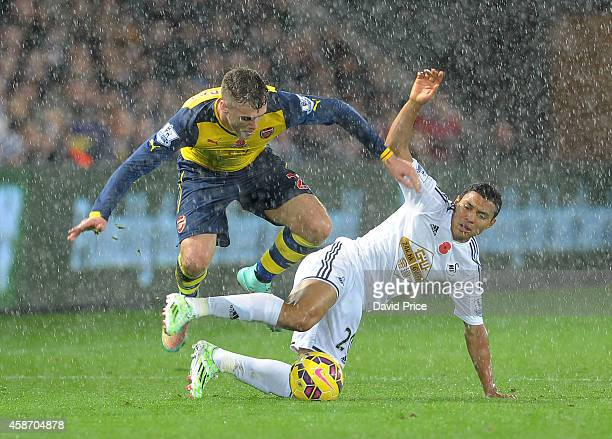 Calum Chambers of Arsenal skips over Jefferson Montero of Swansea during the match between Swansea and Arsenal in the Barclays Premier League at...