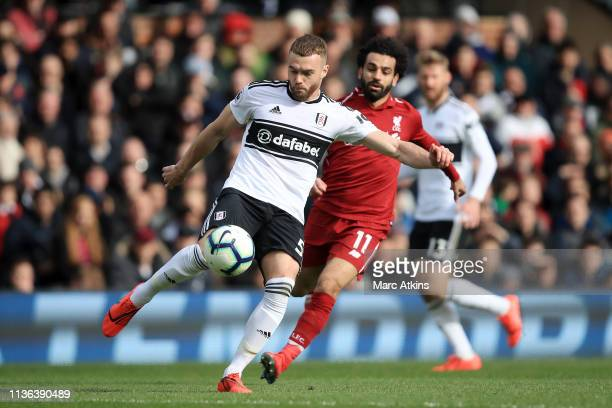 Calum Chambers of Fulham controls the ball as Mohamed Salah of Liverpool looks on during the Premier League match between Fulham FC and Liverpool FC...
