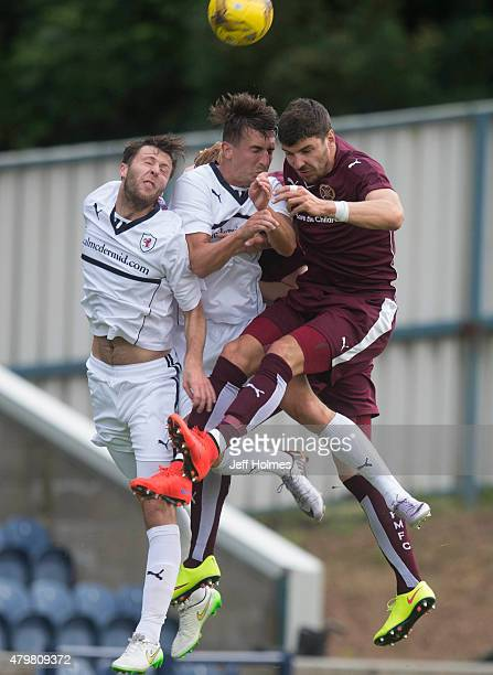 Calum Paterson of Hearts gets the better of Lewis Toshney and Grant Anderson of Raith Rovers during the Pre Season Friendly between Raith Rovers and...