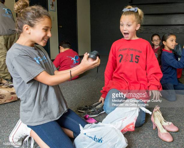 Calvary Christian School fourth grader Chantelle Andronesi left holds up a donated child's shoe and exclaims 'How cute' as her classmate Amanda McKee...