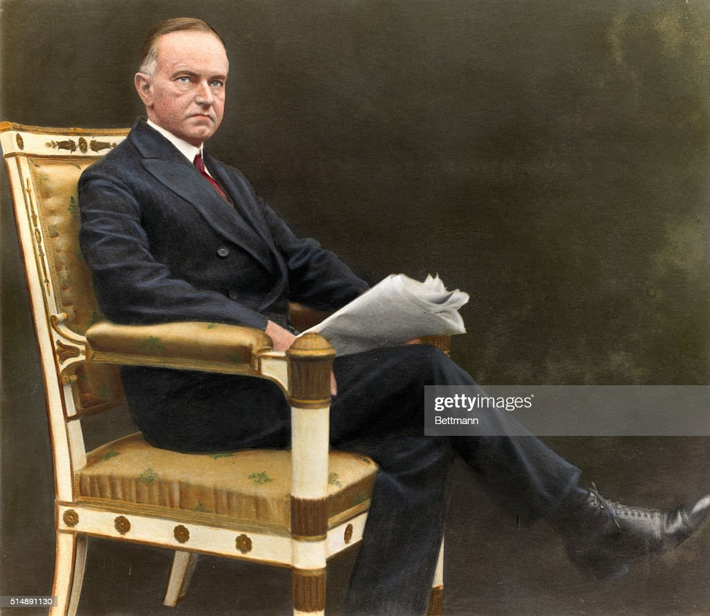 President Calvin Coolidge Sitting with Newspaper : News Photo