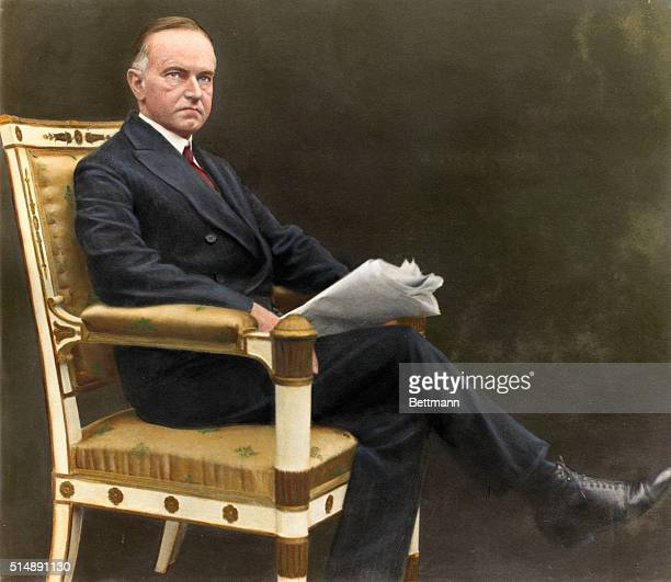 Calvin Coolidge is shown seated reading a newspaper Colored photograph ca 1920s