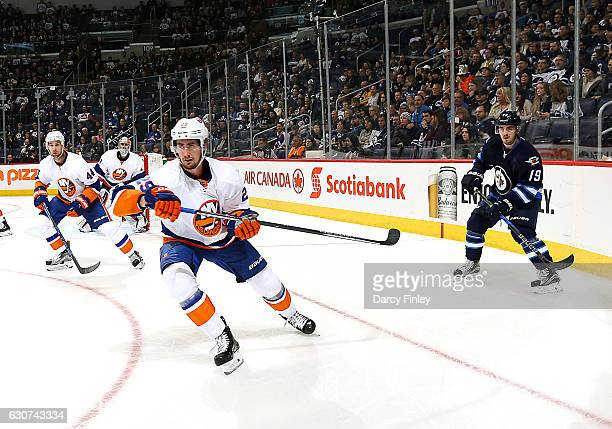 Calvin de Haan goaltender Thomas Greiss Brock Nelson of the New York Islanders and Nic Petan of the Winnipeg Jets keep an eye on the play during...