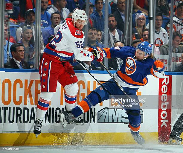 Calvin de Haan of the New York Islanders checks Mike Green of the Washington Capitals during the first period in Game Three of the Eastern Conference...