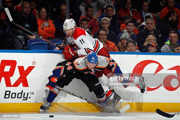 Calvin de Haan of the New York Islanders gets under Jordan Staal of the Carolina Hurricanes during the third period at the Nassau Veterans Memorial...
