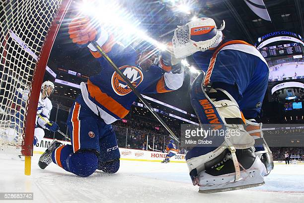 Calvin de Haan of the New York Islanders is knocked into the net by Jonathan Drouin of the Tampa Bay Lightning in Game Four of the Eastern Conference...