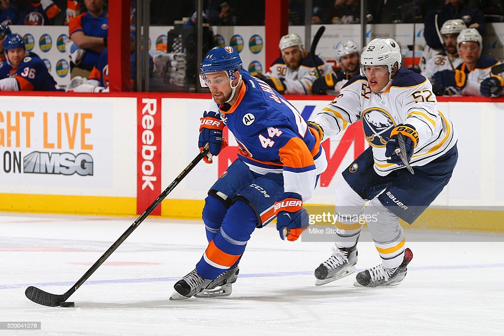 Calvin de Haan #44 of the New York Islanders plays the puck against Hudson Fasching #52 of the Buffalo Sabres at the Barclays Center on April 9, 2016 in Brooklyn borough of New York City.