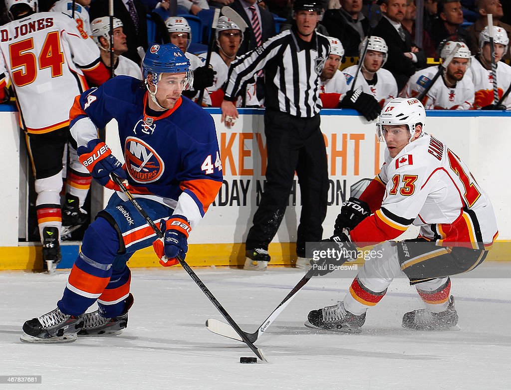 Calvin de Haan #44 of the New York Islanders skates against Mike Cammalleri #13 of the Calgary Flames at Nassau Veterans Memorial Coliseum on February 6, 2014 in Uniondale, New York.