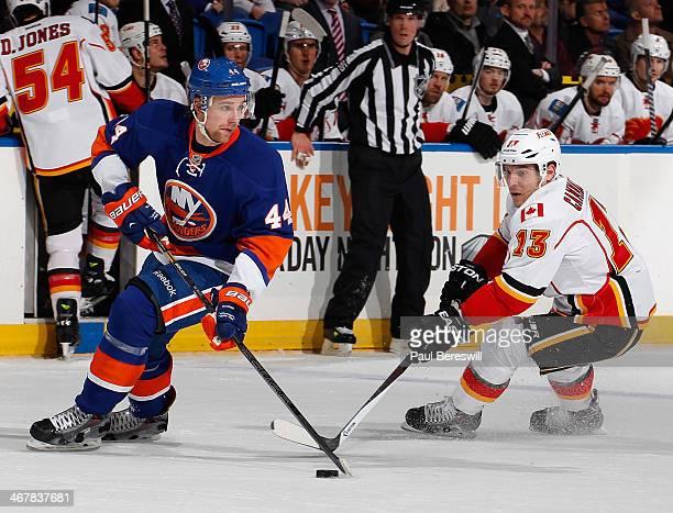 Calvin de Haan of the New York Islanders skates against Mike Cammalleri of the Calgary Flames at Nassau Veterans Memorial Coliseum on February 6,...