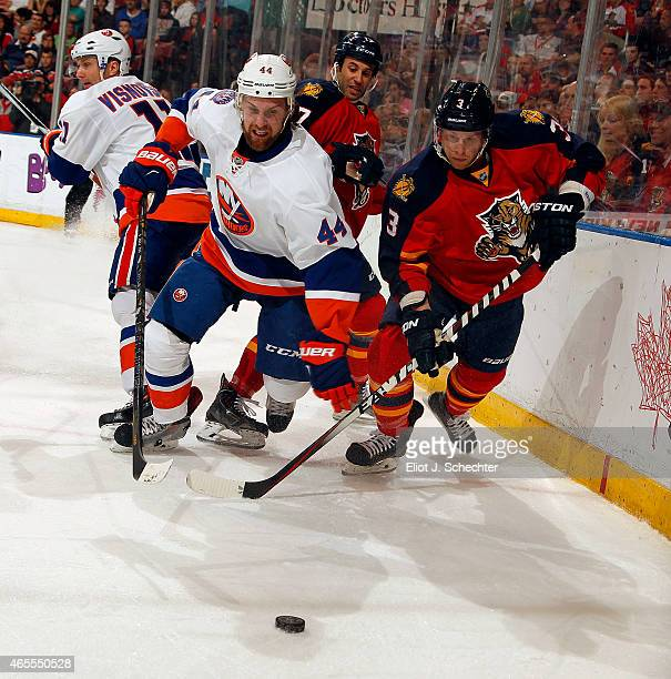 Calvin de Haan of the New York Islanders skates for possession against Steven Kampfer of the Florida Panthers at the BBT Center on March 7 2015 in...