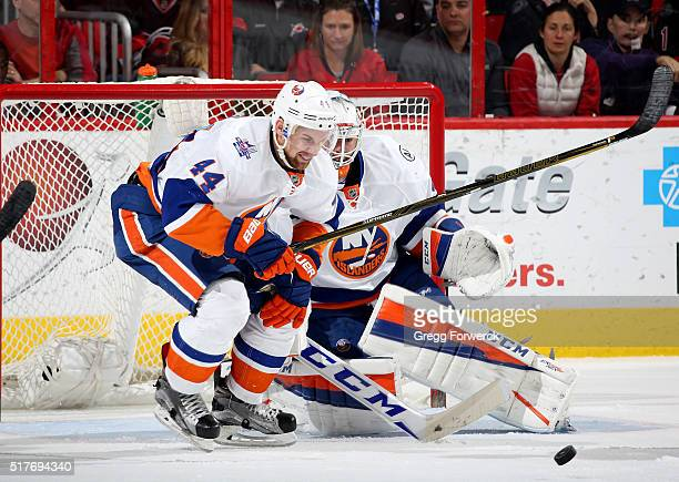 Calvin de Haan of the New York Islanders takes a puck to the knee in front of goaltender JeanFrancois Berube during an NHL game against the Carolina...