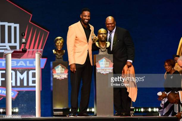 Calvin Johnson and Derrick Moore pose with Johnsons bust during the NFL Hall of Fame Enshrinement Ceremony at Tom Benson Hall Of Fame Stadium on...