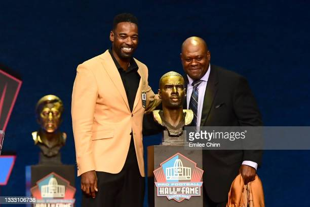 Calvin Johnson and Derrick Moore pose with Johnson's bust during the NFL Hall of Fame Enshrinement Ceremony at Tom Benson Hall Of Fame Stadium on...