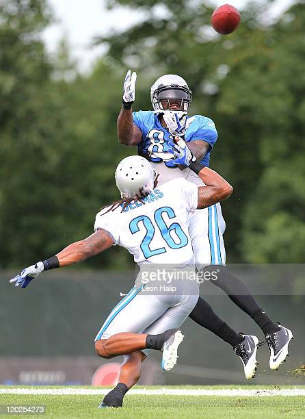 Calvin Johnson and Louis Delmas of the Detroit Lions run through the passing drills during training camp at the Detroit Lions Headquarters and...