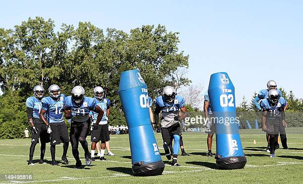 Calvin Johnson, Nate Burleson and Titus Young of the Detroit Lions work out during the morning practice session on July 29, 2012 in Allen Park,...