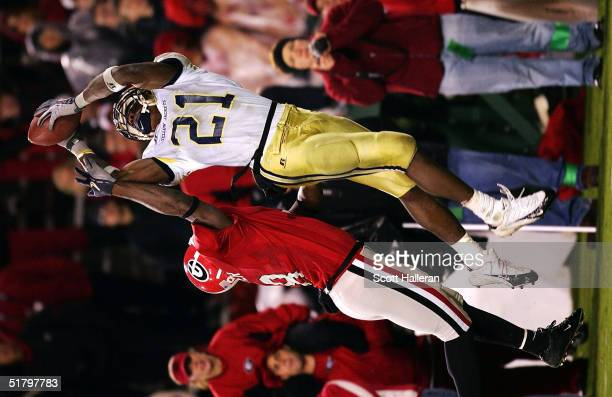 Calvin Johnson of Georgia Tech leaps for the football as Paul Oliver of Georgia defends during the game between Georgia and Georgia Tech on November...