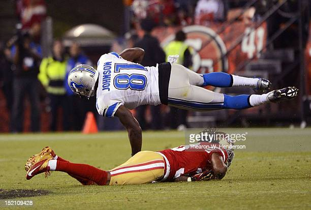 Calvin Johnson of the Detroit Lions after a twenty six yard pass play has his legs cut from under him by Dashon Goldson of the San Francisco 49ers...