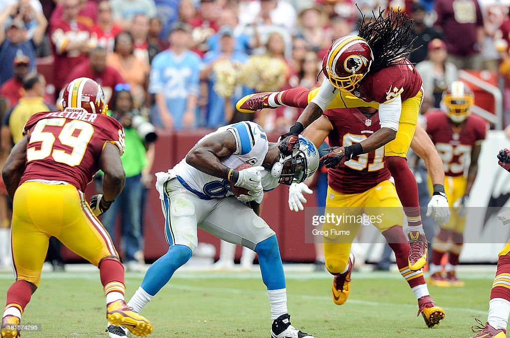 Calvin Johnson #81 of the Detroit Lions breaks a tackle by Brandon Meriweather #31 of the Washington Redskins and scores a touchdown in the fourth quarter at FedExField on September 22, 2013 in Landover, Maryland. Detroit won the game 27-20.
