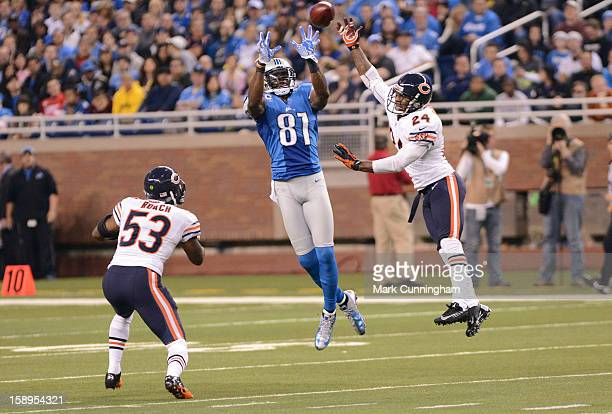 Calvin Johnson of the Detroit Lions jumps into the air to catch a pass in front of Nick Roach and Kelvin Hayden of the Chicago Bears during the game...