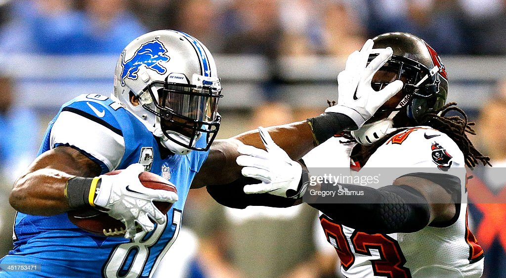 Calvin Johnson #81 of the Detroit Lions stiff arms Mark Barron #23 of the Tampa Bay Buccaneers in the second quarter at Ford Field on November 24, 2013 in Detroit, Michigan.