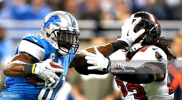 Calvin Johnson of the Detroit Lions stiff arms Mark Barron of the Tampa Bay Buccaneers in the second quarter at Ford Field on November 24 2013 in...